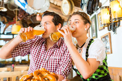 Couple drinking beer in bavarian restaurant Stock Photography