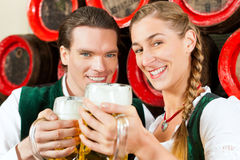 Couple drinking beer in brewery. Young couple, men and women, in traditional Bavarian Tracht drinking beer in a brewery in front of beer barrels Stock Images