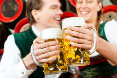 Couple drinking beer in brewery. Young couple, men and women, in traditional Bavarian Tracht drinking beer in a brewery in front of beer barrels Stock Image