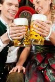 Couple drinking beer in brewery. Young couple, men and women, in traditional Bavarian Tracht drinking beer in a brewery in front of beer barrels Royalty Free Stock Image