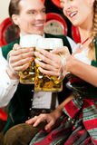 Couple drinking beer in brewery. Young couple, man and woman, in traditional Bavarian Tracht drinking beer in a brewery in front of beer barrels Stock Images