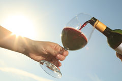 A couple drinking a bottle of red wine outside Stock Photography