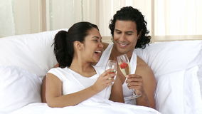 Couple drinking champagne in bed. Happy couple drinking champagne in bed celebrating an anniversary. Footage in high definition stock video