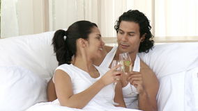 Couple drinking champagne in bedroom. Happy couple drinking champagne in bedroom celebrating an anniversary. Footage in high definition stock footage