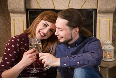 Couple drinking of champagne hugging together near fireplace Royalty Free Stock Photography