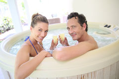 Couple drinking champagne in jacuzzi Stock Photos