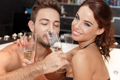 Couple drinking champagne in jacuzzi Royalty Free Stock Image