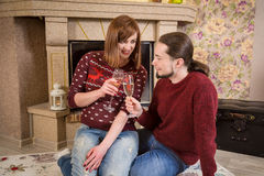 Couple drinking of champagne and sitting together near fireplace Stock Photography