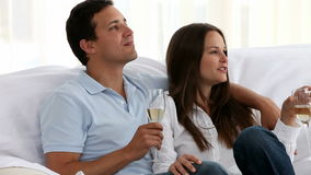 Couple drinking Champagne together. Sitting on the sofa stock video