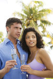Couple drinking champagne on tropical holiday Stock Images