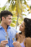 Couple drinking champagne on tropical holiday Stock Photo