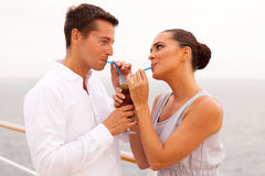 Couple drinking cocktail. Romantic young couple drinking cocktail together on a cruise ship royalty free stock image