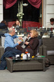 Couple drinking a cocktail sitting in the outdoor coffee bar. TRIESTE, ITALY - APRIL, 28: Couple drinking a cocktail sitting in the outdoor coffee bar on April stock photography