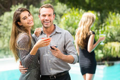 Couple drinking cocktail by swimming pool at party. Cheerful young couple drinking cocktail by swimming pool at party royalty free stock photo