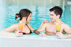 Couple drinking a cocktail by the swimming pool Stock Photo