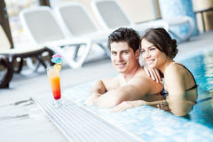 Couple drinking a cocktail by the swimming pool and relaxing Stock Image