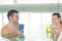 Couple drinking cocktail by swimming pool and relaxing stock photo