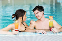 Couple drinking a cocktail by the swimming pool and relaxing Royalty Free Stock Images