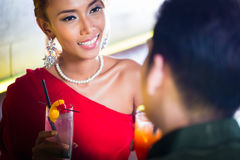 Couple drinking cocktails in fancy bar. Asian couple drinking cocktails in fancy bar Royalty Free Stock Image