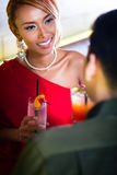 Couple drinking cocktails in fancy bar. Asian couple drinking cocktails in fancy bar Royalty Free Stock Photo