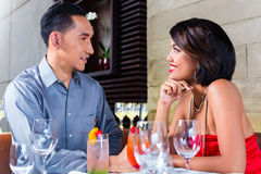 Couple drinking cocktails in fancy bar. Asian couple drinking cocktails in fancy bar royalty free stock images