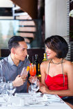 Couple drinking cocktails in fancy bar. Asian couple drinking cocktails in fancy bar Stock Photo