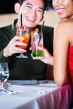Couple drinking cocktails in fancy bar. Asian couple drinking cocktails in fancy bar Royalty Free Stock Photography