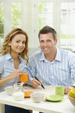 Couple drinking coffee. At home, sitting at breakfast table, marking newspaper Royalty Free Stock Photos