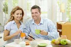 Couple drinking coffee. At home, sitting at breakfast table, marking newspaper Royalty Free Stock Image