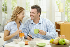 Couple drinking coffee. Happy couple drinking coffee at home, sitting at breakfast table, looking at each other, smiling Royalty Free Stock Image