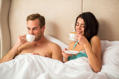 Couple drinking coffee in bed. Stock Photo