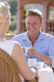 Couple drinking coffee on cafe patio Royalty Free Stock Image