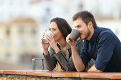 Couple drinking coffee contemplating views. Happy couple drinking coffee contemplating views outdoors in a town outskirts royalty free stock photography