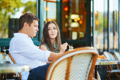 Couple drinking coffee and eating croissants in Paris, France royalty free stock images