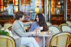 Couple drinking coffee and eating croissants in Parisian cafe. Romantic dating couple drinking coffee and eating traditional French croissants in cafe in Paris stock images