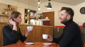 Couple drinking coffee on a first date in a coffee shop. Slow motion. stock footage