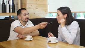 Couple drinking coffee laughing in cafe stock footage