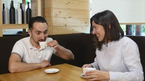 Couple drinking coffee laughing in cafe stock video footage