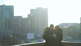 Couple drinking coffee outside in winter day. Young man and young woman drinking coffee on a street of a city in cold winter day stock video footage