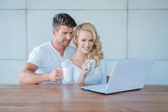 Couple drinking coffee and reading on a laptop Stock Image