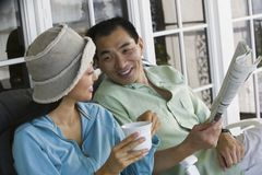 Couple drinking coffee and reading newspaper on porch Royalty Free Stock Photography