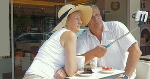 Couple drinking coffee and taking selfie on smartphone stock video footage