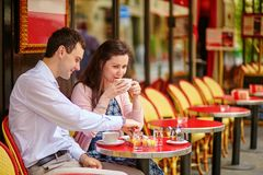 Couple drinking coffee or tea in a Parisian cafe. Happy couple drinking coffee or tea in a Parisian outdoor cafe Stock Photography