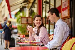 Couple drinking coffee or tea in a Parisian cafe Stock Images