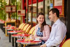 Couple drinking coffee or tea in a Parisian cafe. Happy couple drinking coffee or tea in a Parisian outdoor cafe Royalty Free Stock Images