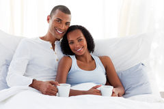Couple drinking a coffee on their bed. Smiling Afro-American couple drinking a coffee on their bed Royalty Free Stock Images