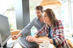 Couple drinking coffee and websurfing in a coffee shop Royalty Free Stock Images