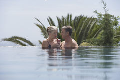 Couple Drinking Daiquiri In Outdoor Pool. Happy mature couple drinking daiquiri in outdoor pool Stock Photography