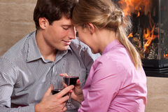 Couple drinking by fire Royalty Free Stock Image