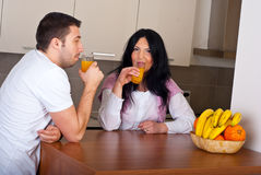 Couple drinking fresh orange juice in kitchen Stock Images